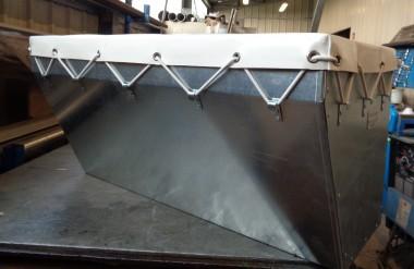 Bac de stockage réalisé en feuille d'acier galvanisé pliées et soudées, équipé d'une bâche renforcée pour garantir l'étanchéité en cas de pluie.