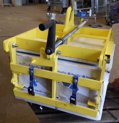 Pince spécifique réalisée pour la manipulation manuelle de cartons, les pinces sont activées grâce à des roulements coniques mis en route lors d'une rotation de la poignée.